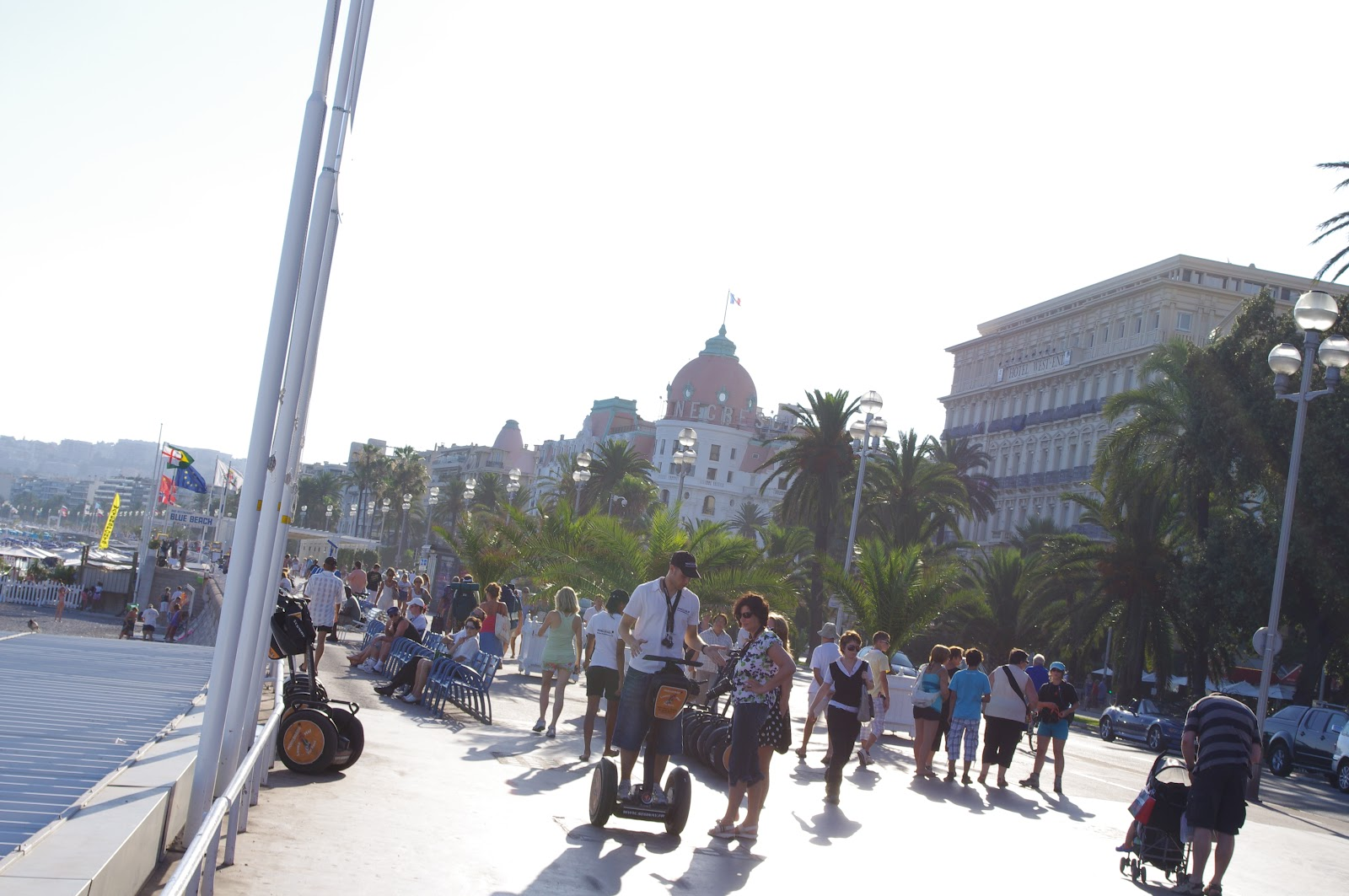 promenade des anglais, large boardwalk filled with tourists in nice, cote d'azur, south of france. Tourists and segway tours, palm trees and luxury hotels in the distance on a sunny day in the french riviera