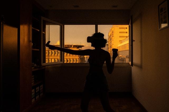 Pessoal jogando com game de simulação, em frente a janela de seu apartamento, como se estivesse se exercitando.