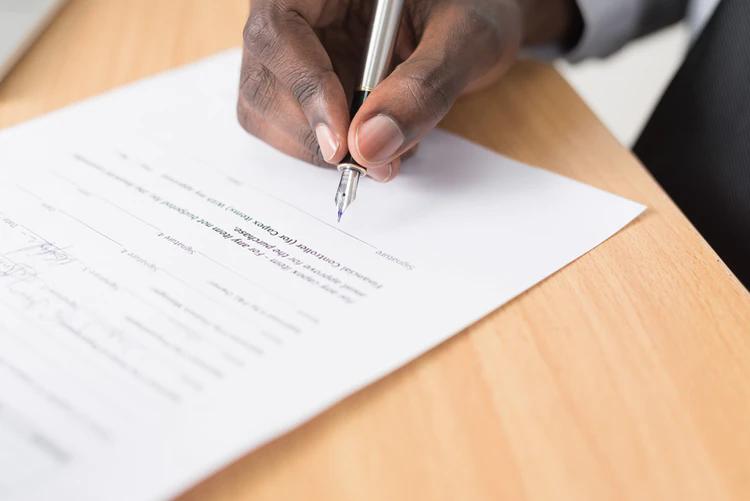 A imagem mostra um contrato sendo assinado, e uma mão segurando uma caneta de ponta fina próxima à linha de assinatura do documento.