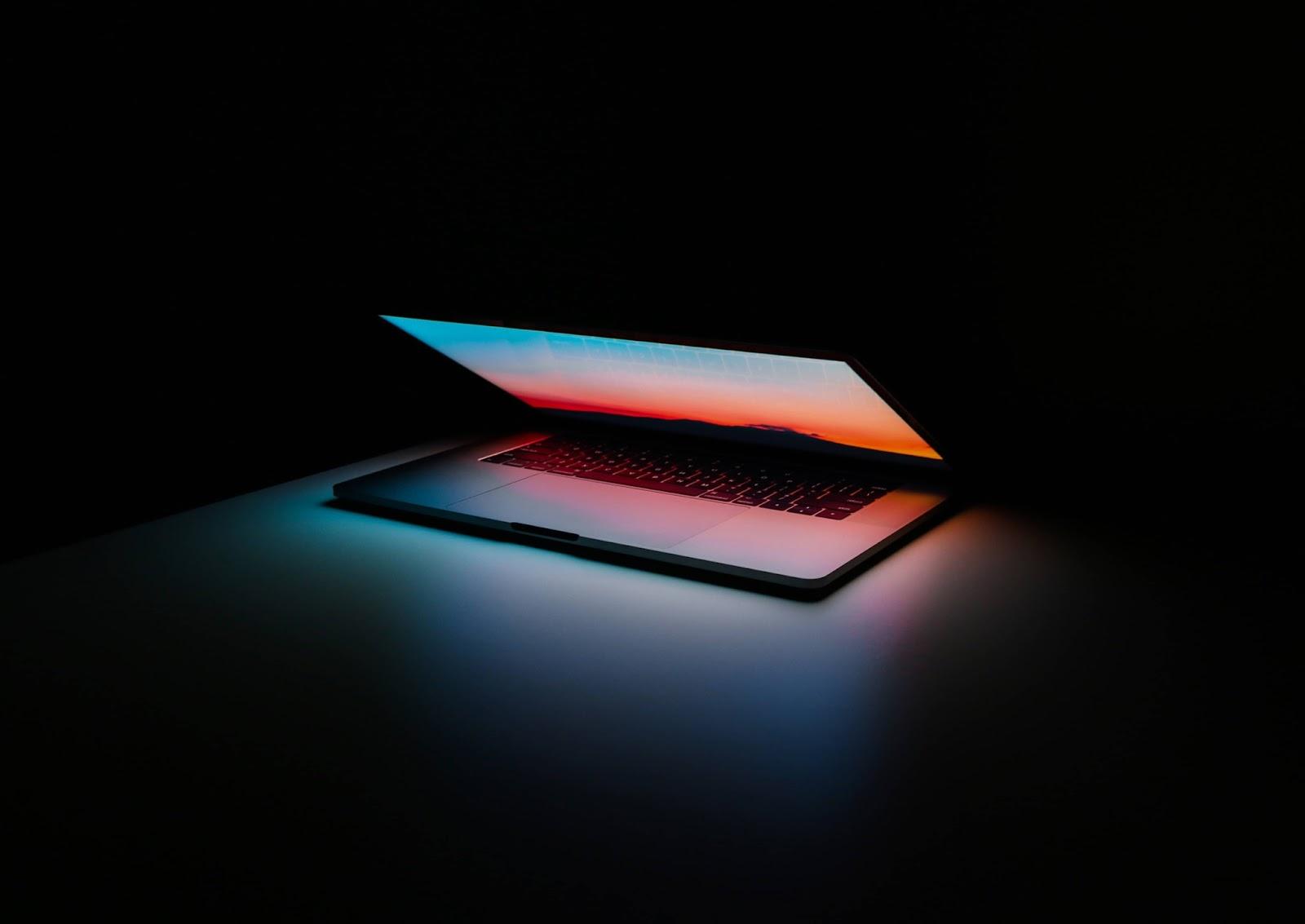 Foto di un computer grigio in accensione appoggiato su una superficie nera