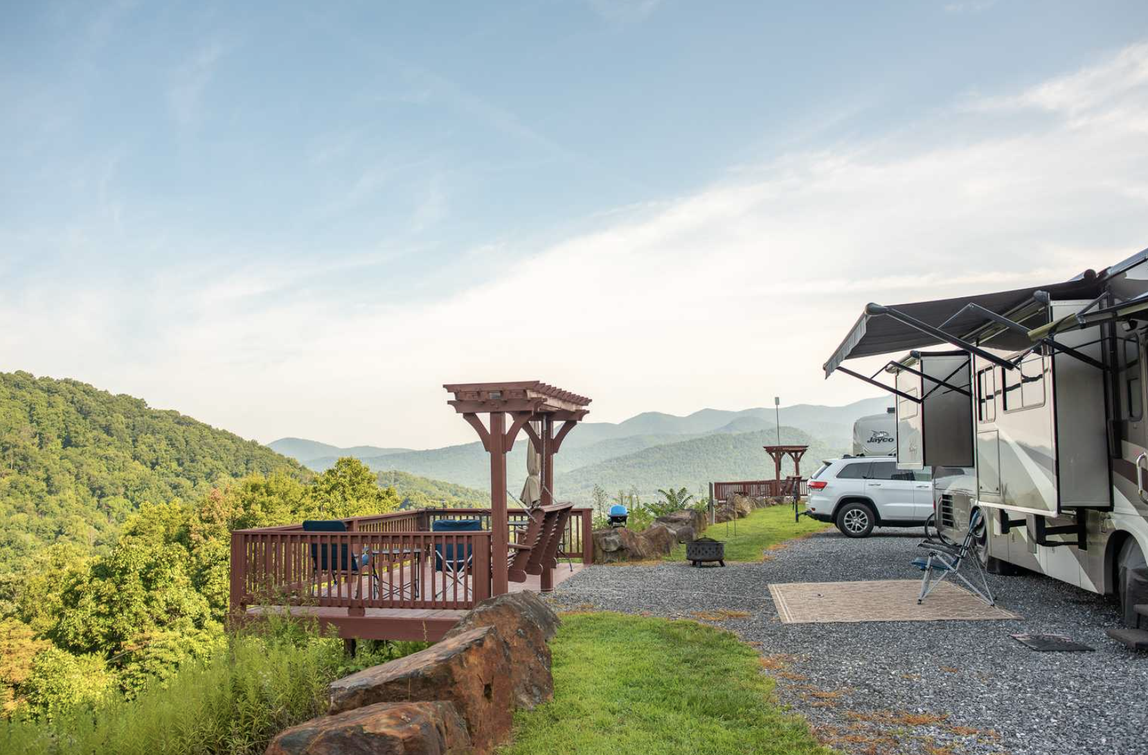 RV parked at campground with mountains in background.