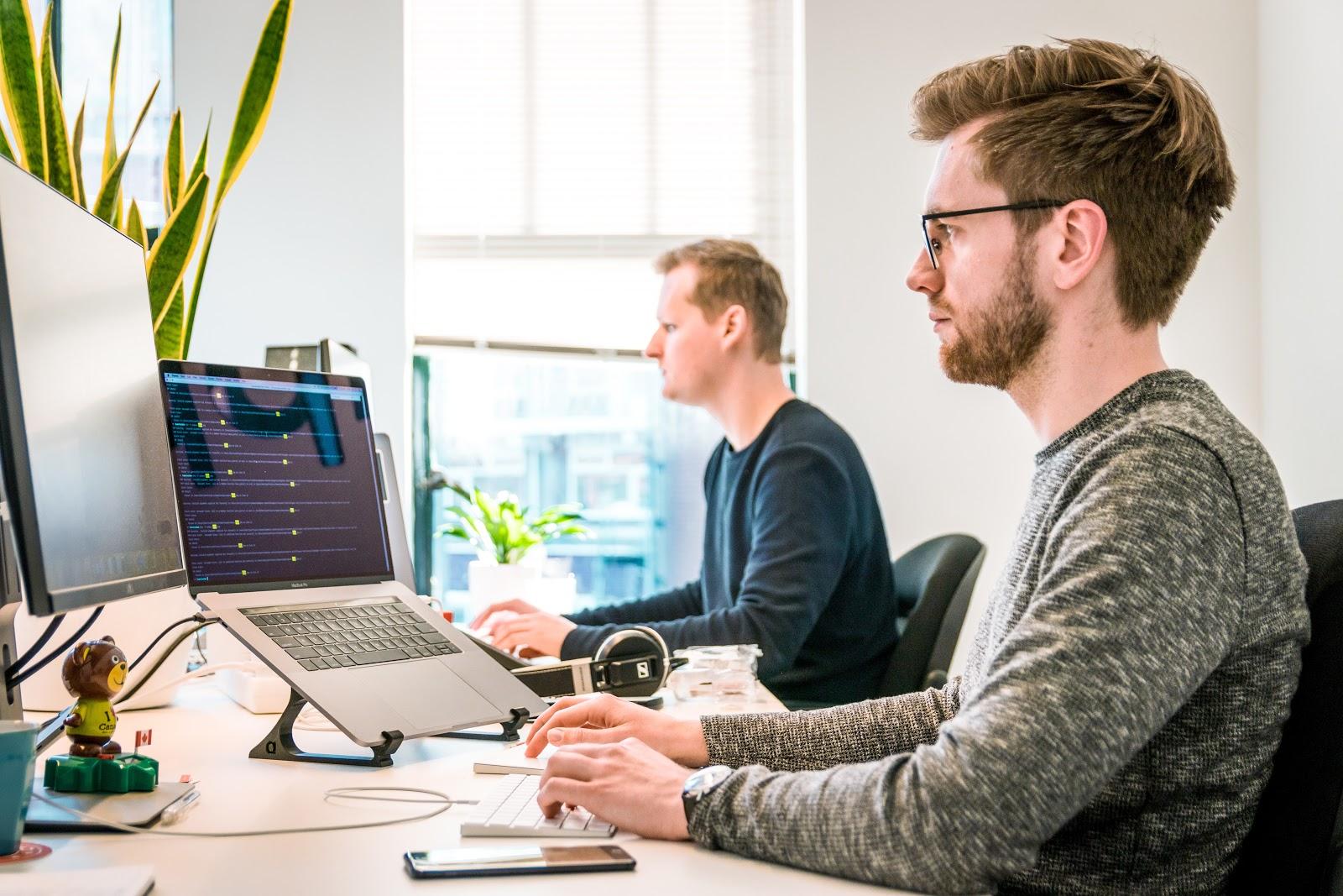 Duas pessoas sentadas digitando em um computador.