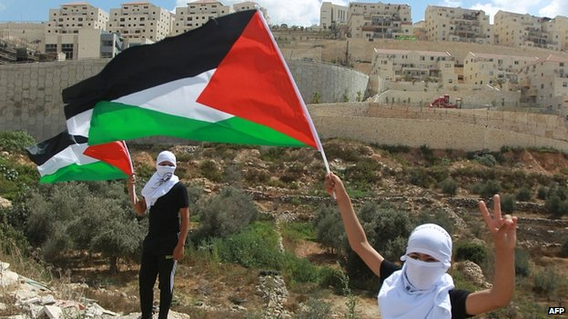 Palestinian protesters wave the national flag, in front of the Israeli settlement of Beitar Illit. 26 Sept 2014