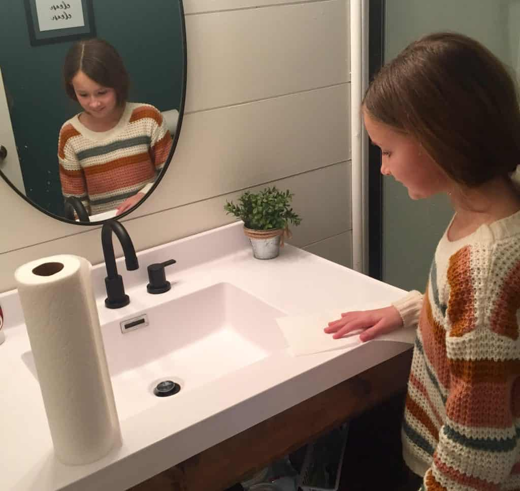 Age appropriate chores for 7-9 year olds: Photo of a 7-9 year old girl wiping off the bathroom sink