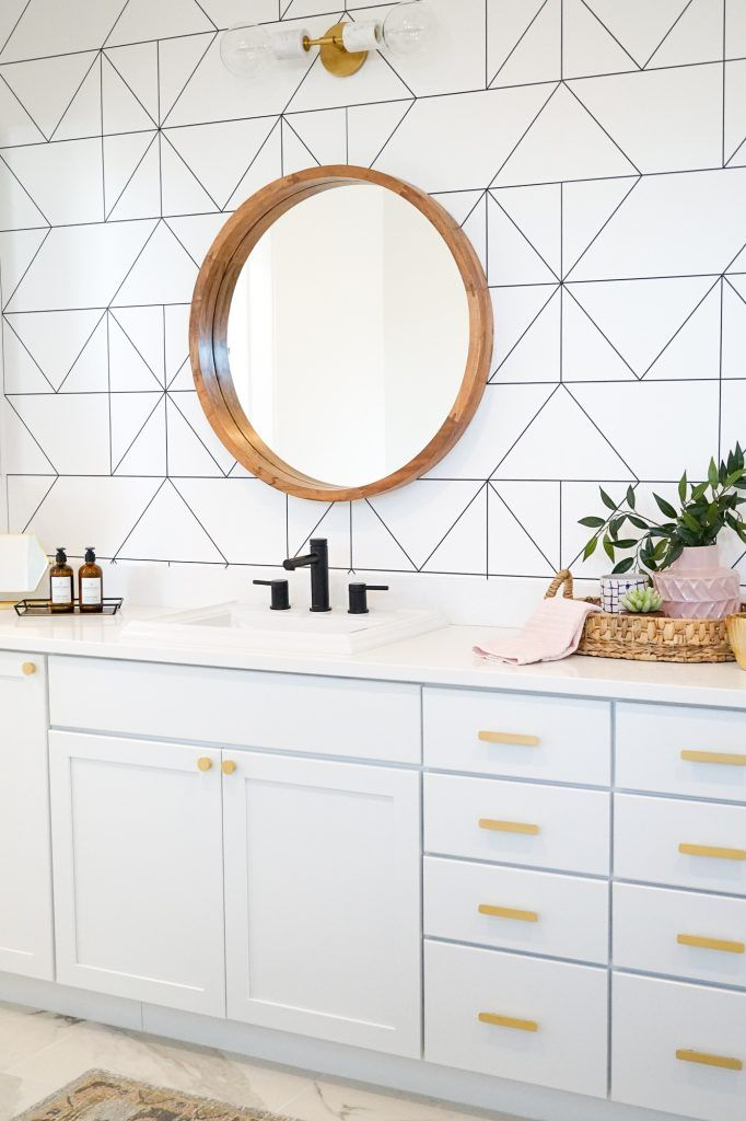 light blue modern vanity cabinets with white geometric wallpaper, circular mirror and white countertops