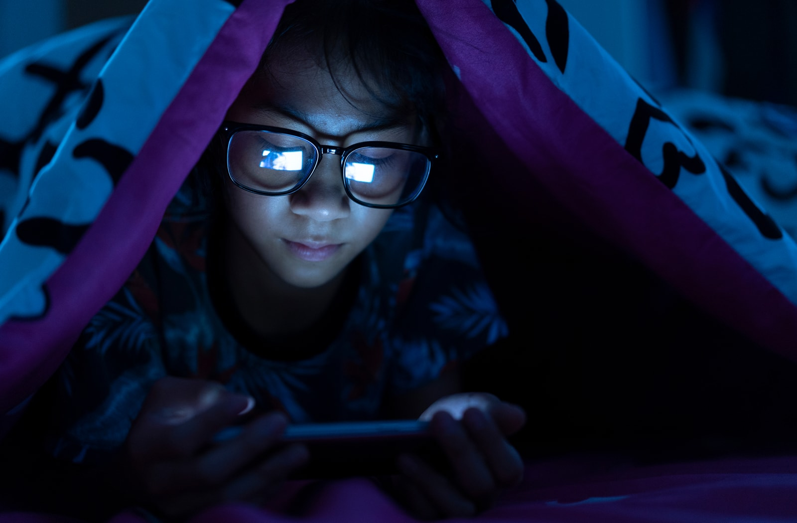 Child playing on phone under his blanket with blue light glasses on.