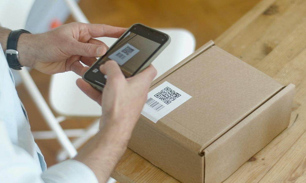 man using smartphone to scan a QR code on a package