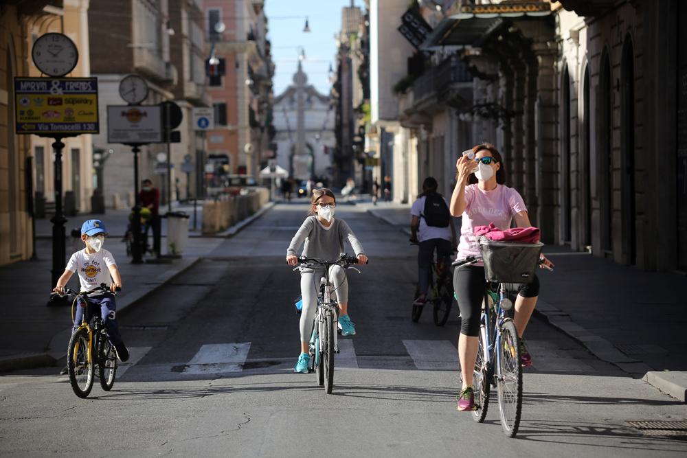 Pessoas andando de bicicleta com máscara de proteção