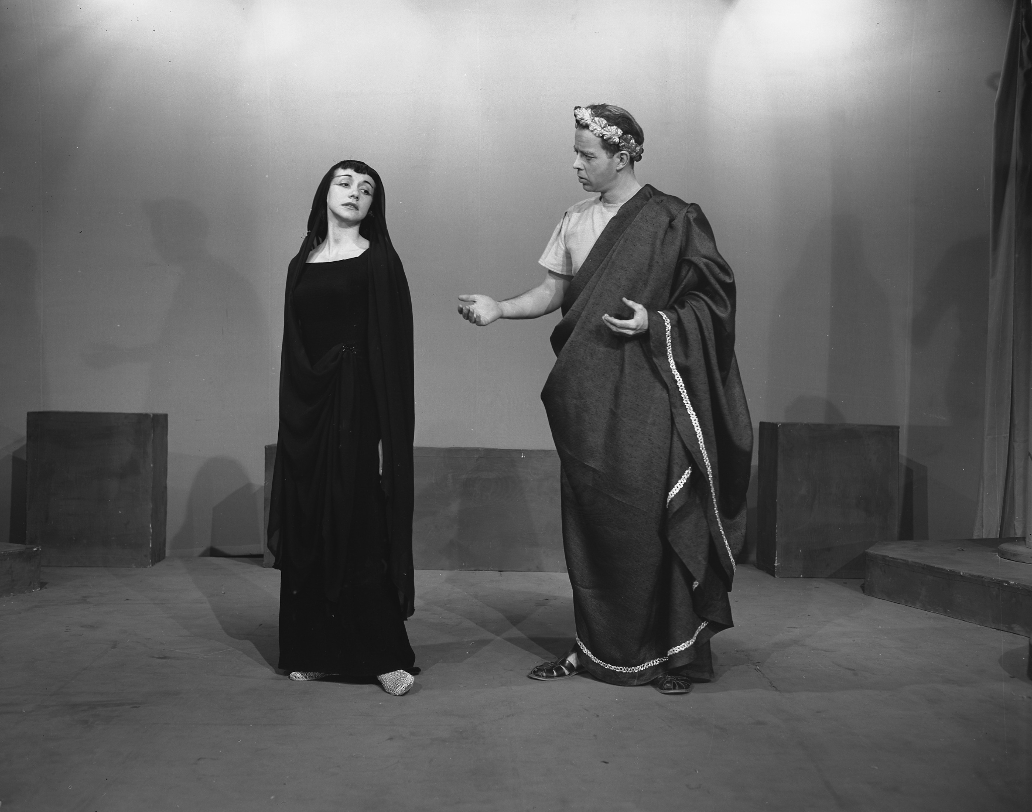 A Caucasian man and woman stand together on stage. The woman wears a long black dress with a black scarf over her hair. She looks over her shoulder as the man speaks to her. He wears a toga and a laurel crown.