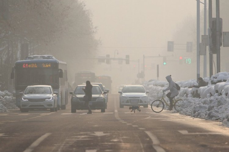 Pedestrians cross a road amidst smog on a polluted day in Nanjing, Jiangsu  province, China January 30, 2018. REUTERS/Stringer