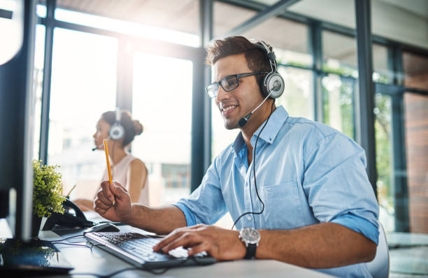 They've got the answers you're looking for Cropped shot of a handsome young man working in a call center with a female colleague in the background service stock pictures, royalty-free photos & images
