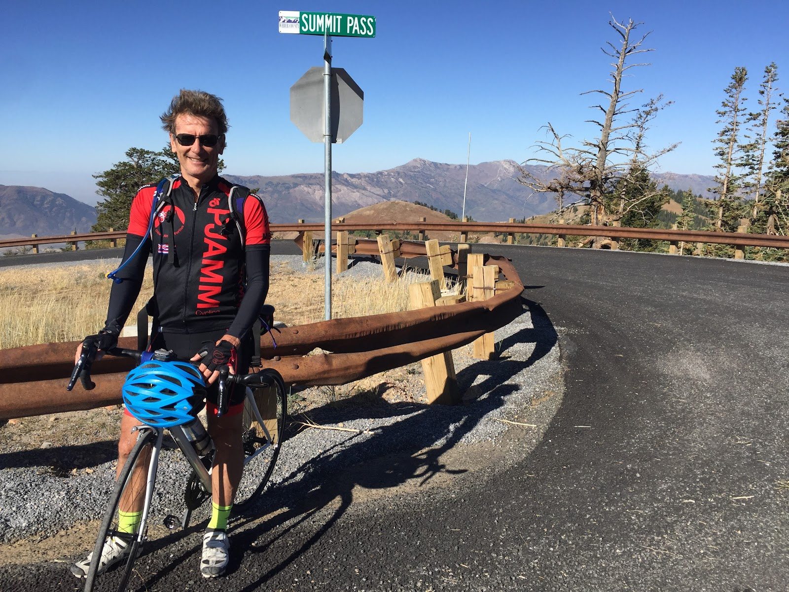 Summit Pass Road Sign with cyclist on Powder Mountain Utah bike climb.