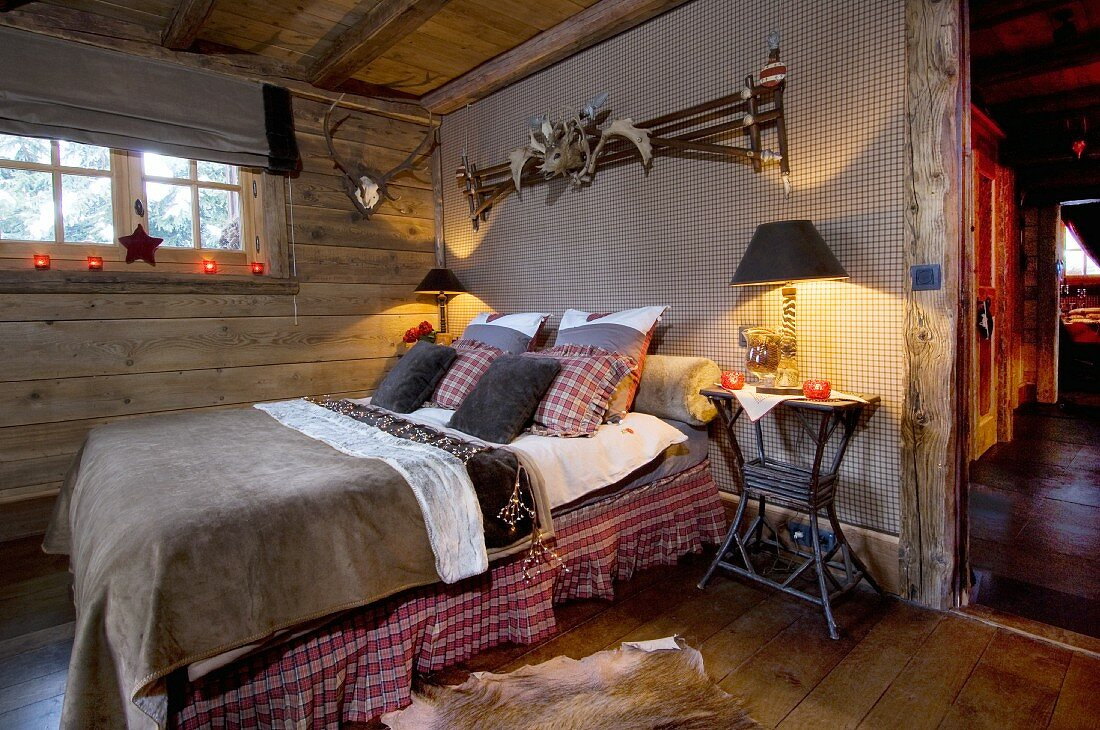 rustic cabin bedroom with red plaid comforter and candles on the windowsill