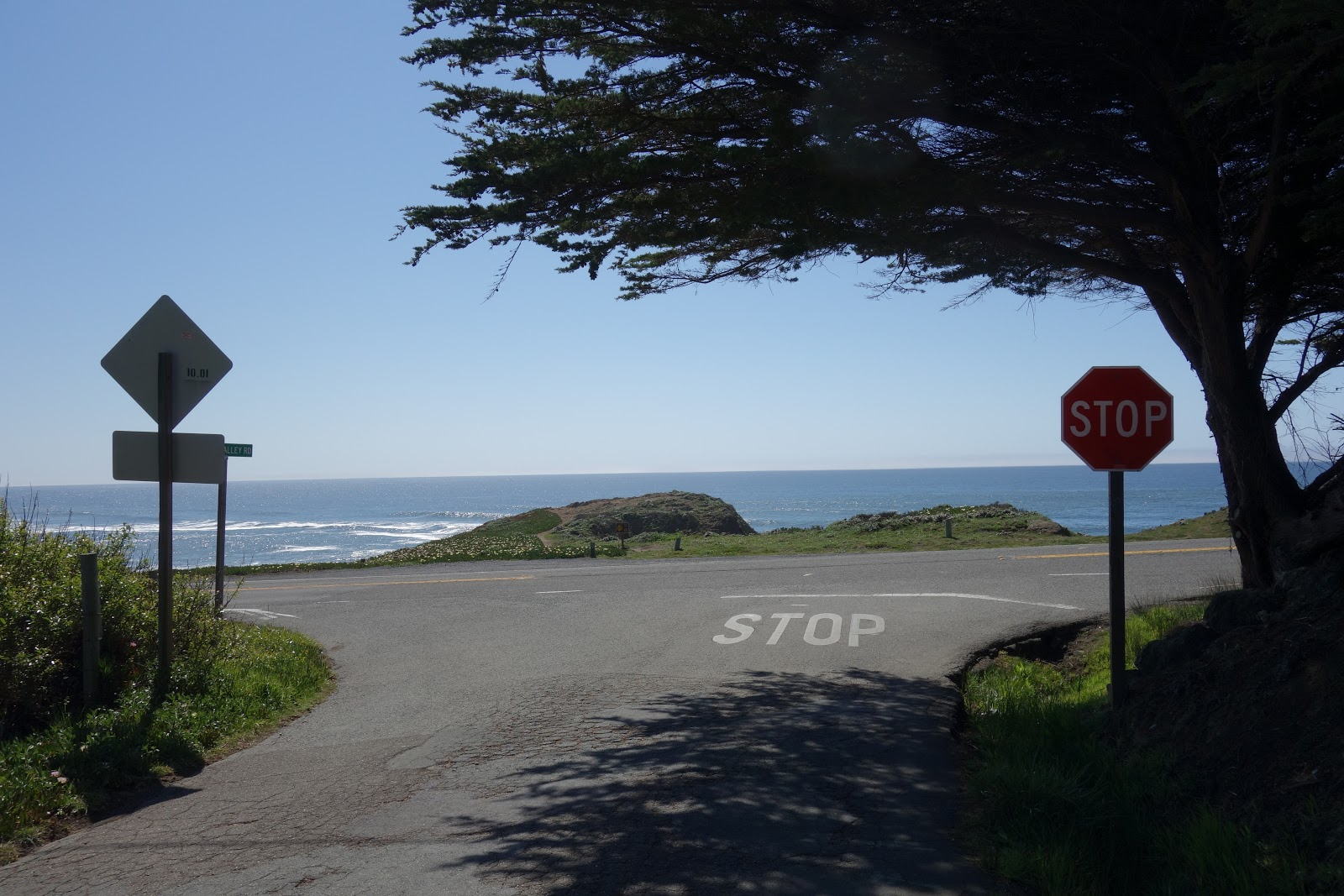 Start of the Coleman Valley Road climb by bike view west to Pacific Ocean, Hwy 1 and road signs.