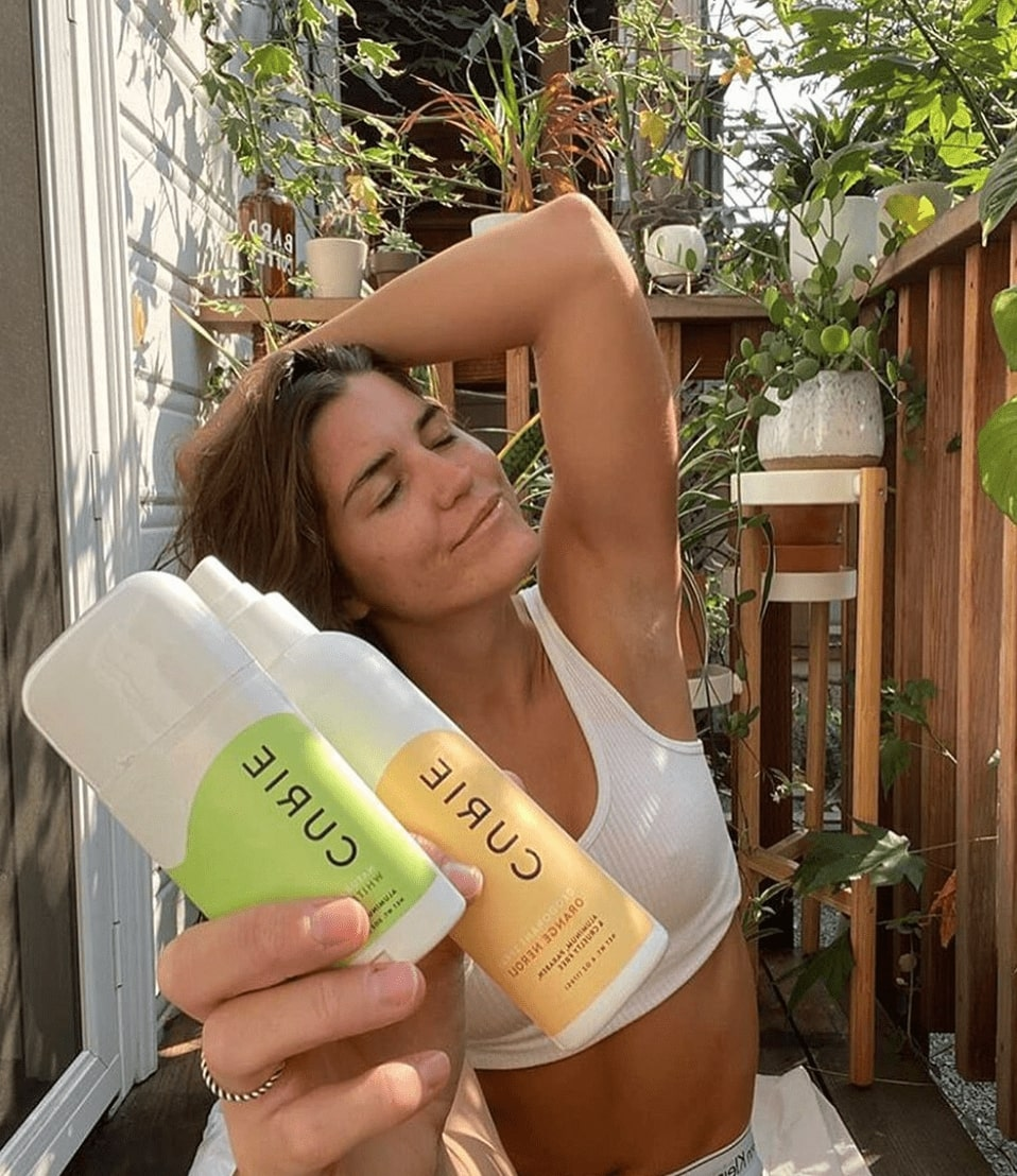 Woman with her arm up to brush her hair back while she smiles with her eyes closed. In her other hand, she is holding a Curie deodorant stick and deodorant spray. The background has a brown fence with potted green plants all around.