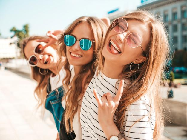Portrait of three young beautiful smiling hipster girls in trendy summer clothes. sexy carefree women posing on the street.positive models having fun in sunglasses.hugging Free Photo