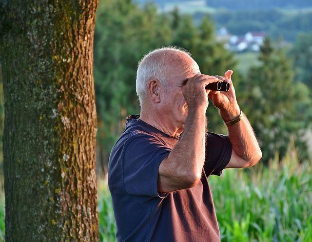 Senior man looking through binoculars, showing why moving from DC to Orange County, VA, after retirement is a good idea