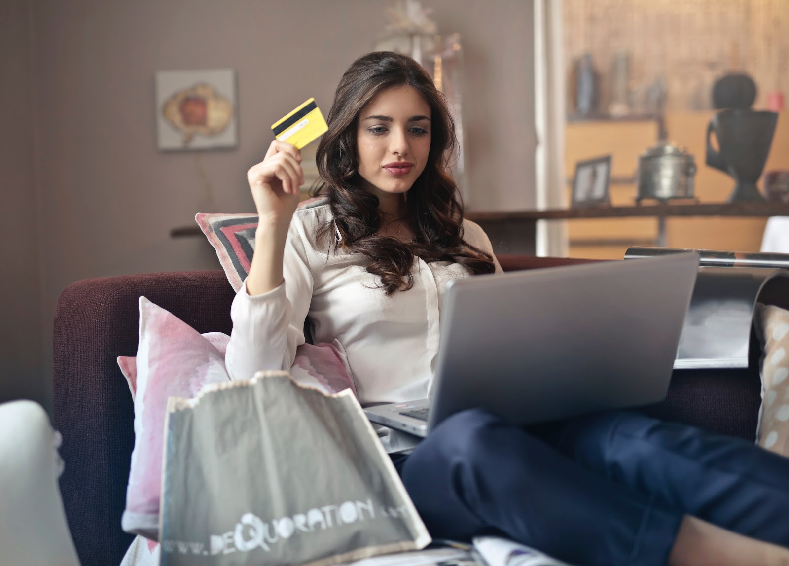 A woman holds a credit card while looking at a laptop