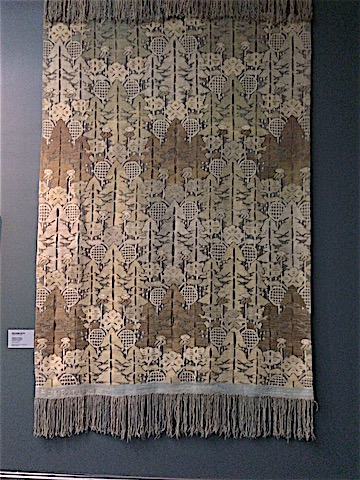 A display of one of Frida Hansen's Art Nouveau textile series Door Curtain, brown in color with horizontal sections