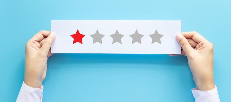 2 mains tiennent une feuille avec une seule étoile rouge sur 5, cela illustre un avis client négatif