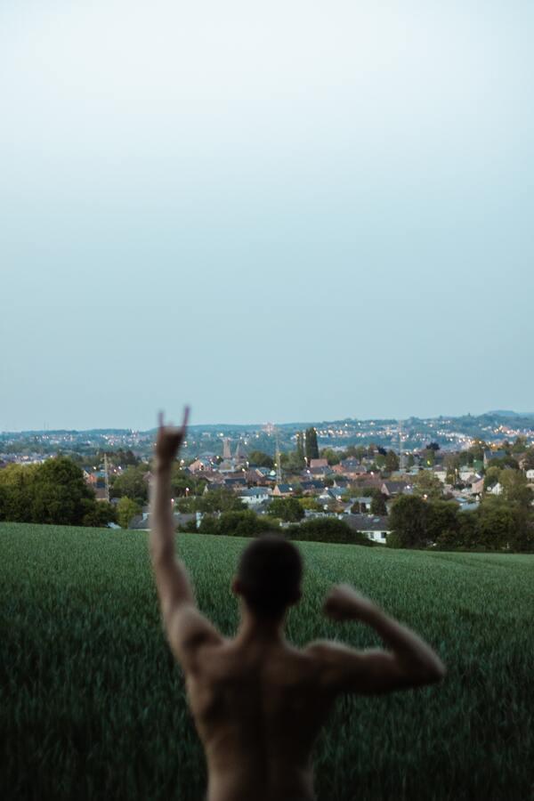 Foto de um cara sem camiseta, com o braço pra cima fazendo o sinal do rock. No fundo, você vê uma paisagem de uma cidade