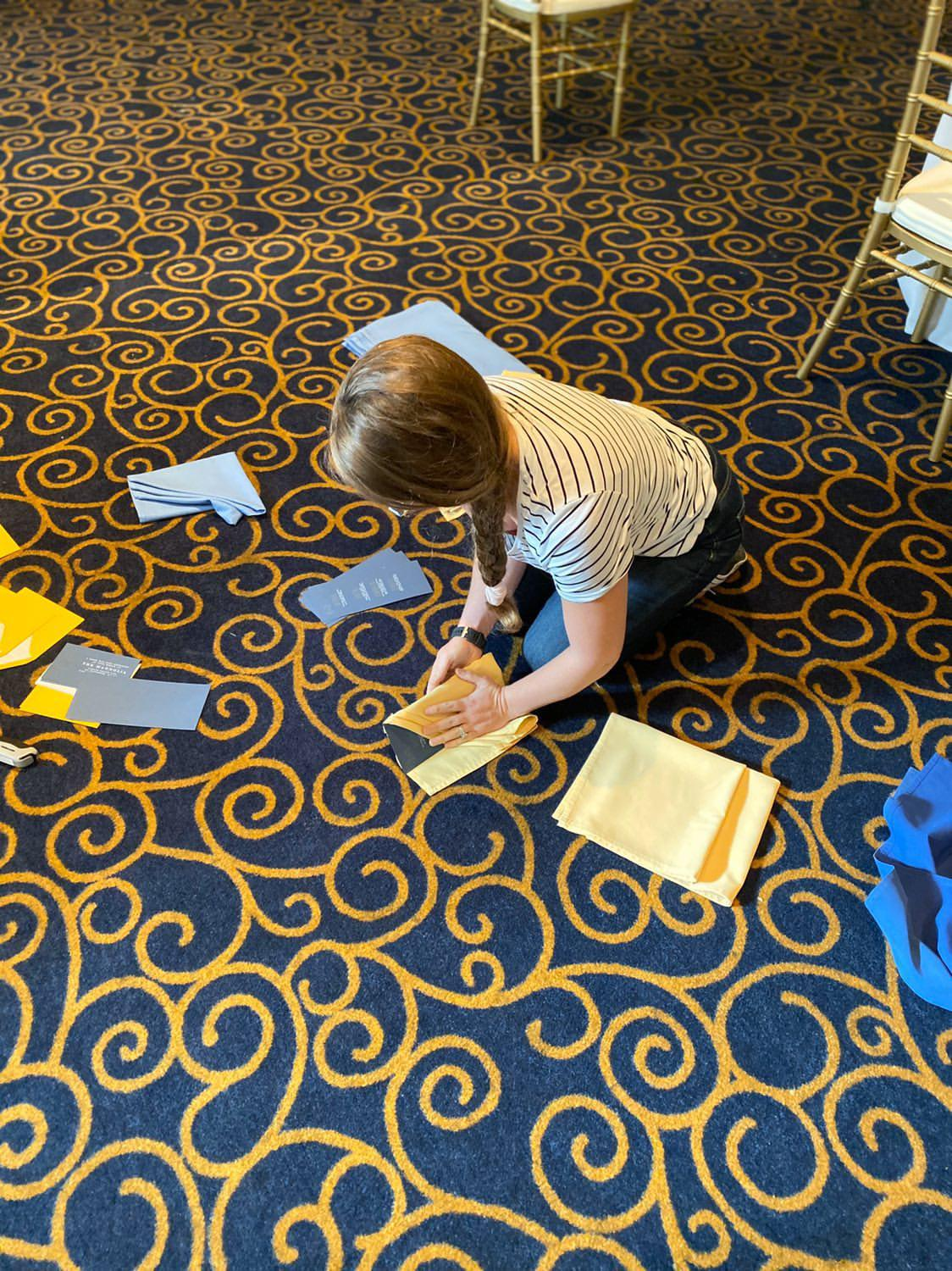 Molly (owner of Beauty Bright Design a boutique stationery design firm) folds custom designed deep blue menus in mustard fabric napkins on the floor of The Paxton Ballroom for a styled wedding shoot in Omaha NE