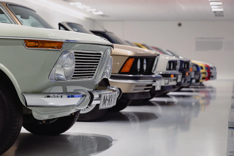Carros clássicos de diversas cores em fila