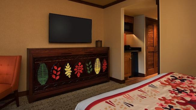 Bed across from chair, wall bed with a fauna design, flat screen tv and ice bucket, next to a kitchenette