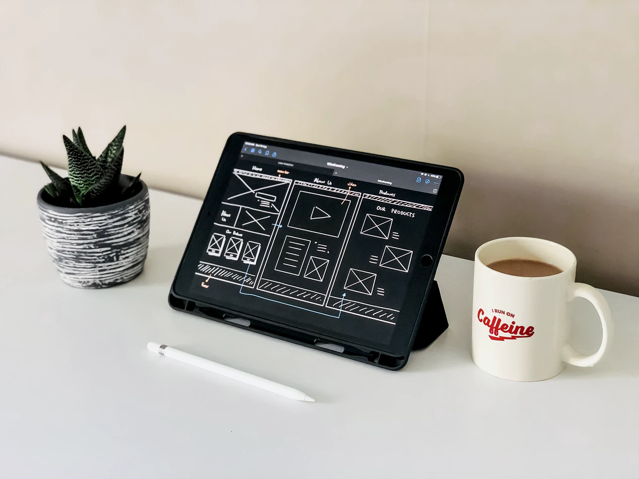 succulent plant, iPad, and a cup of coffee on a table