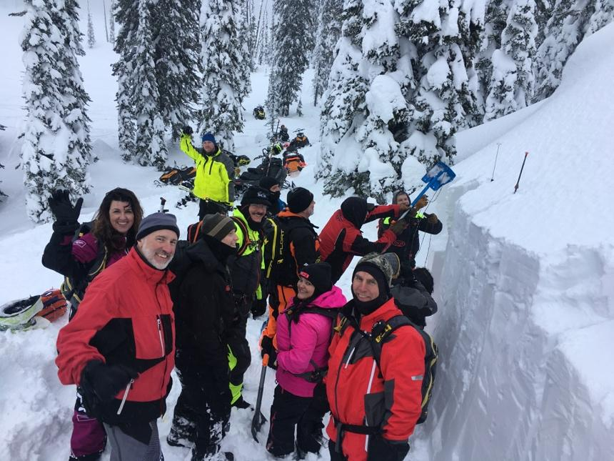 A group of people standing on top of a snow covered slope  Description automatically generated