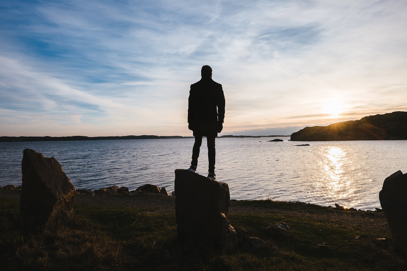 Une personne de dos regardant la vaste expanse de la mer et le coucher du soleil se demandant si ses choix de consommation peuvent avoir un vrai impact sur l'environnement.