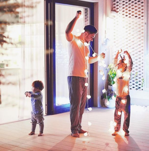 family playing with golden light strings in the house