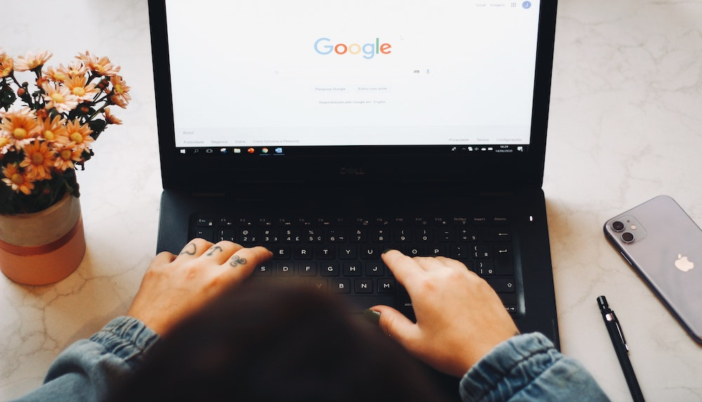 Une femme devant son ordinateur ouvert sur une page de recherche Google