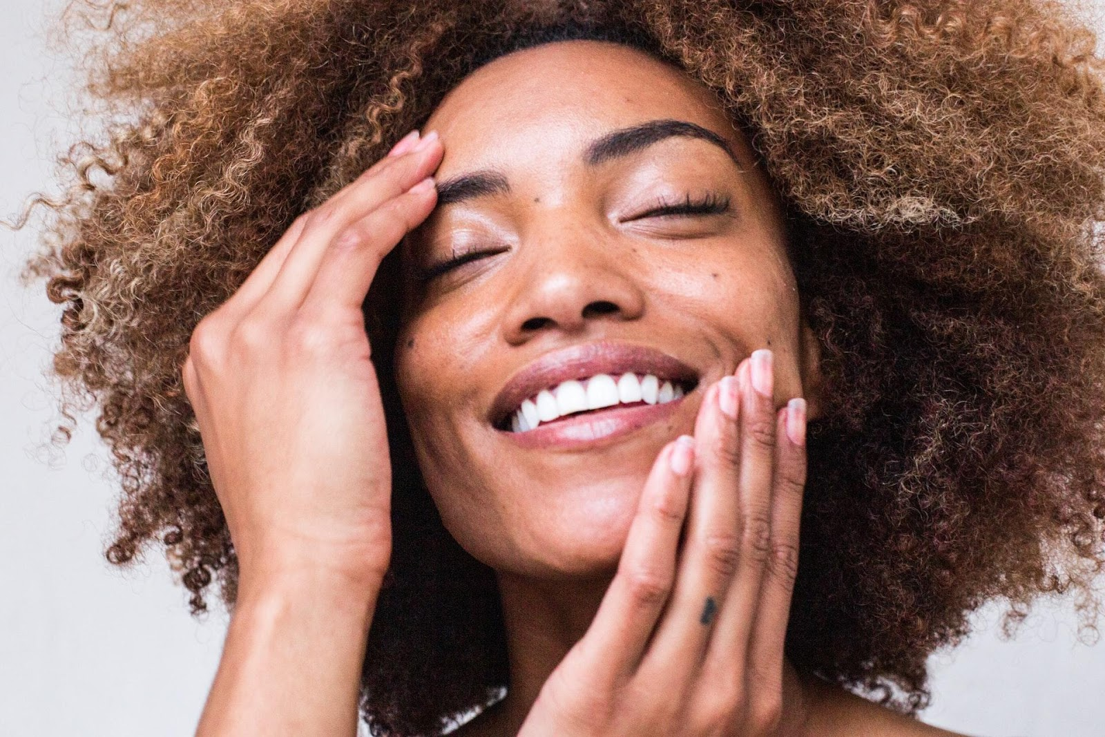 A person smiling with her hands on her face  Description automatically generated with low confidence