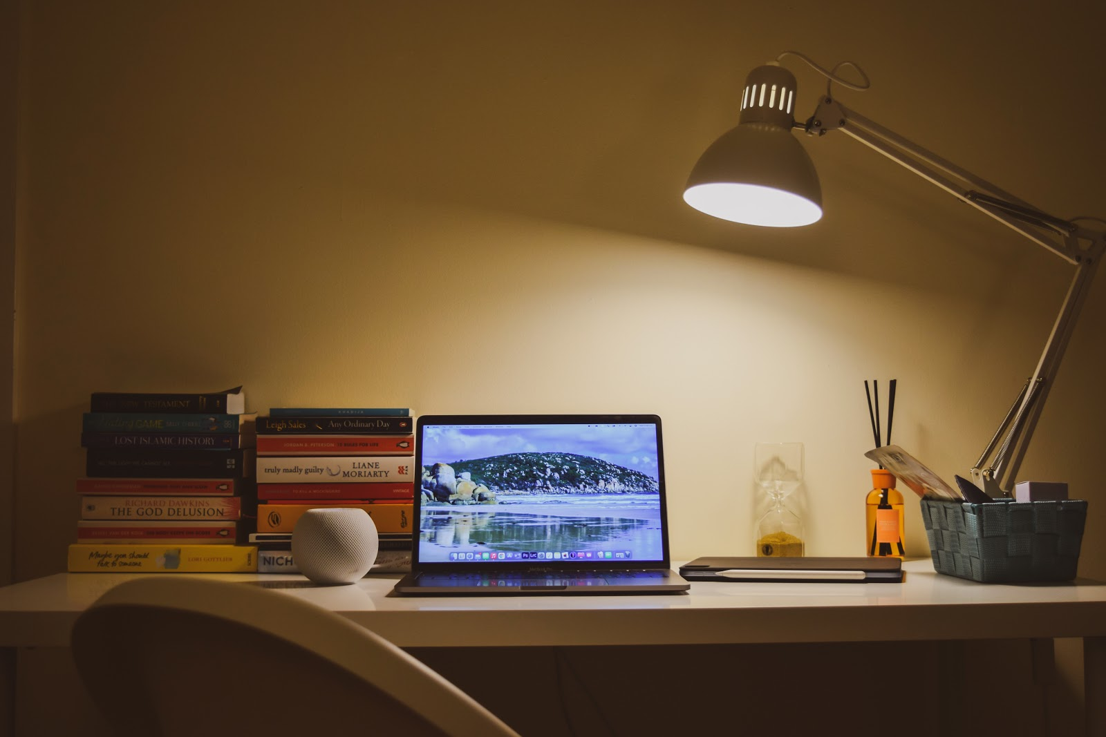 books, laptop, and lamp in a workstation