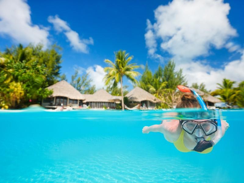 Mulher de mergulho em águas tropicais claras