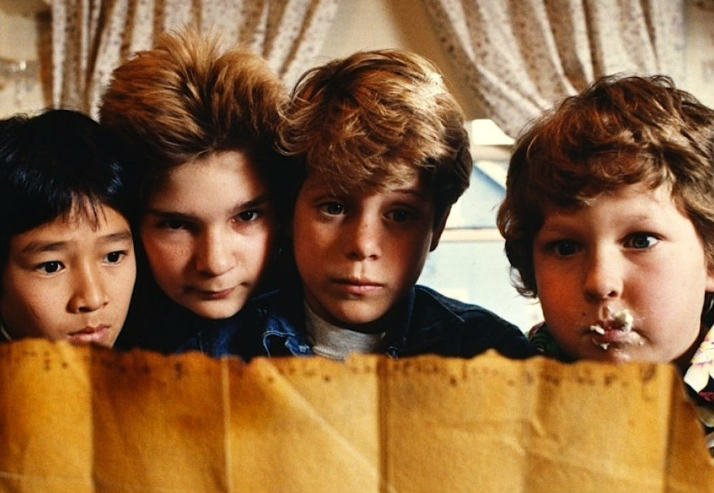 """Image of """"The Goonies"""" cast looking at a treasure map"""