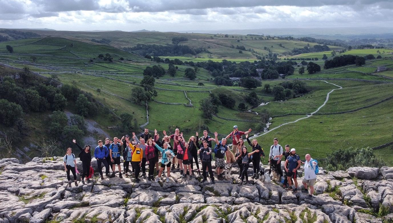 A group of people standing on a hill  Description automatically generated with low confidence