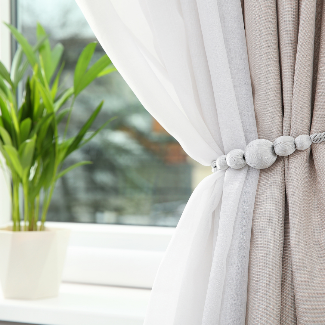 Sheers and drapes held back with an ornate cord frame a window. A green plant rests on the sill.