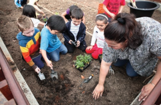 A group of children and their instructor digging in a playground