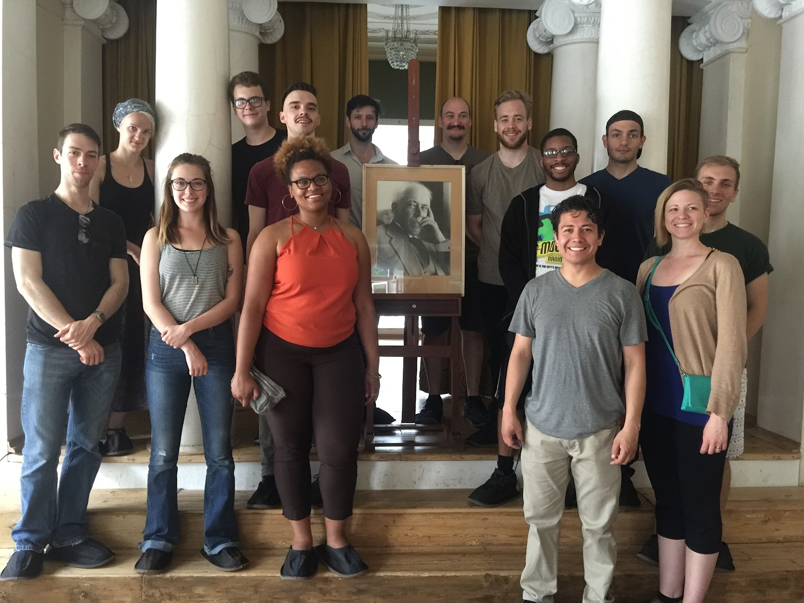WSU Theatre students pose in front of a portrait of Konstantin Stanislavsky in Moscow, Russia