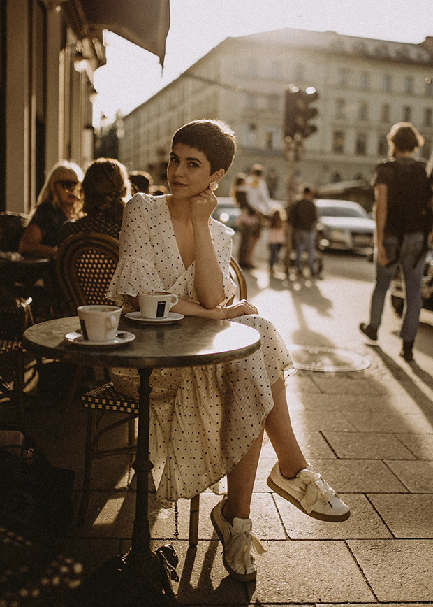 woman sitting in outdoor cafe wearing a white dress with black polka dots. the background behind her is blurred. edited with a sepia tint