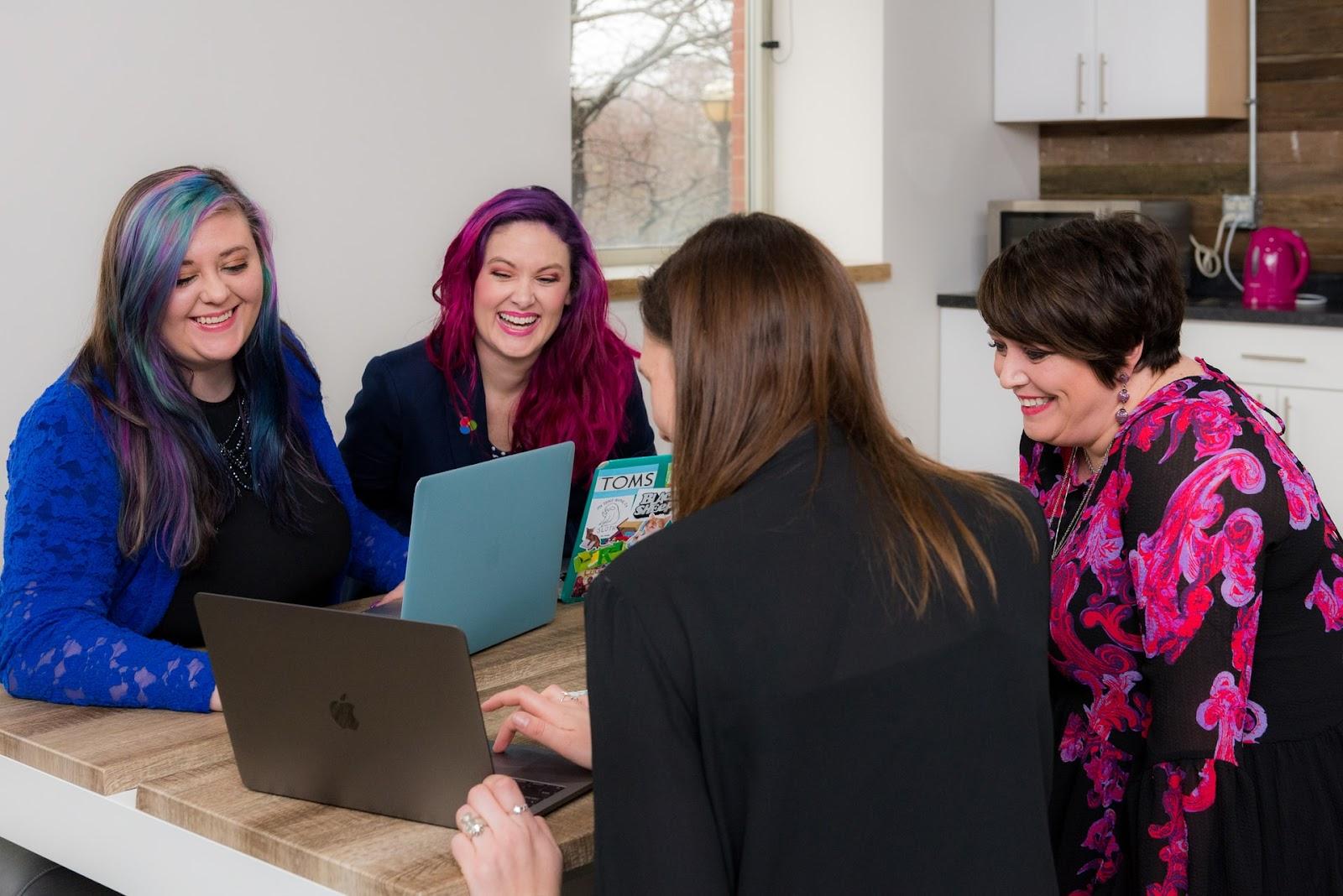 Três mulheres de cabelo colorido conversando.