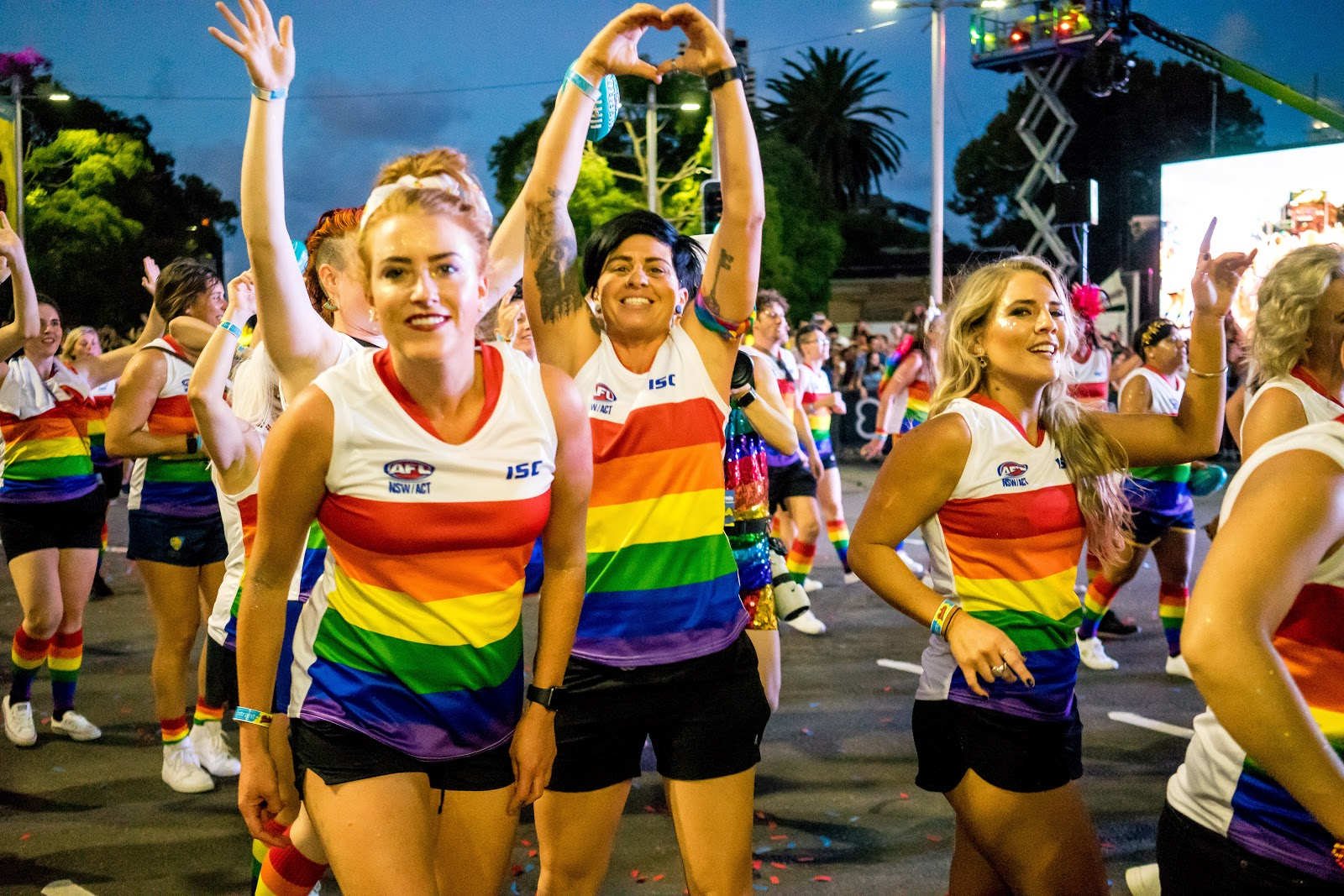 Photo of Mardi Gras parade attendees in colourful AFL uniform