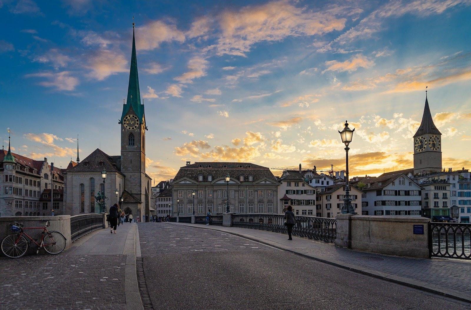 zurich old town bridge medieval church clock tower during sunset switzerland