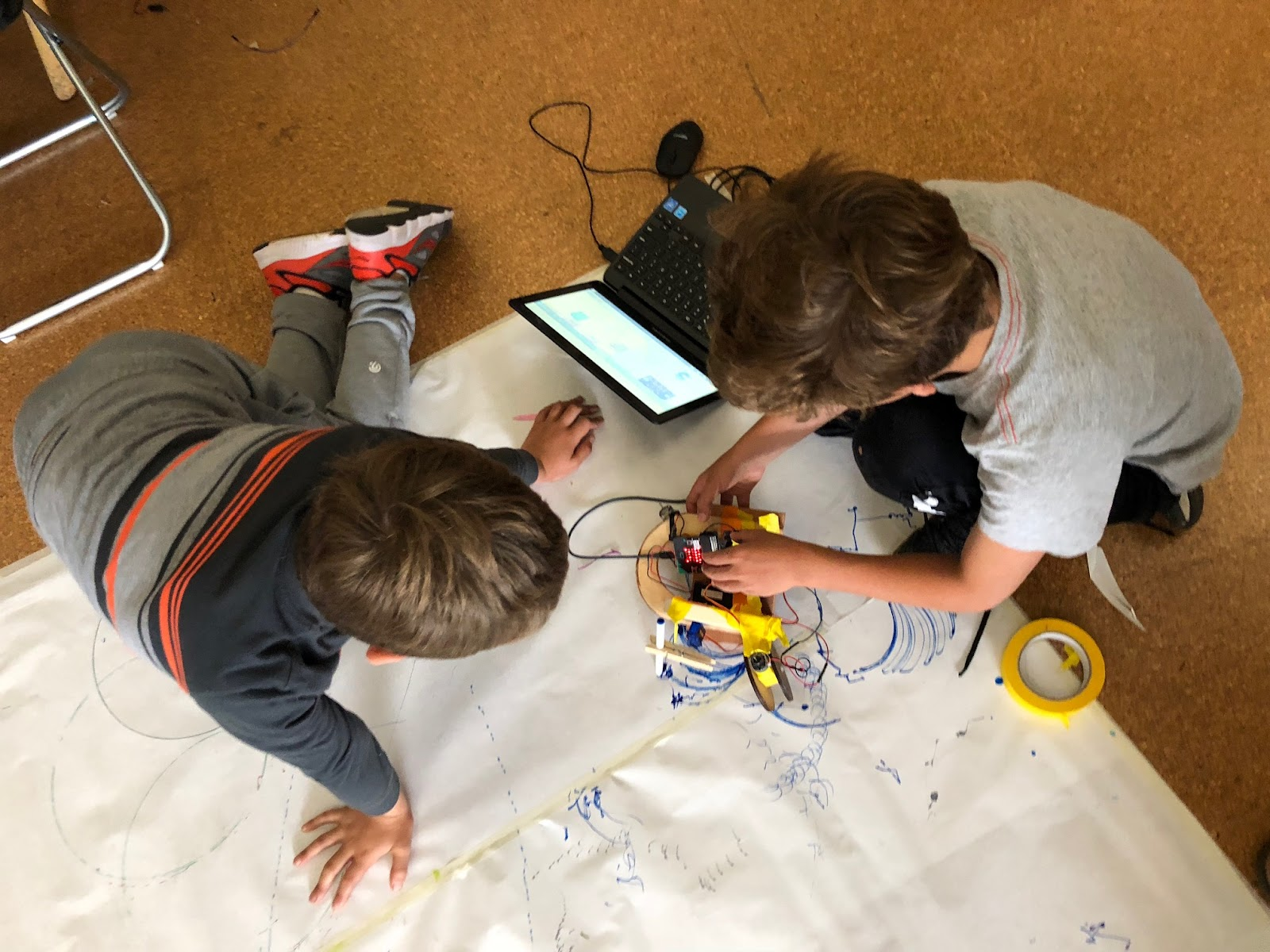 students test their micro:bit and moto:bit drawing bots