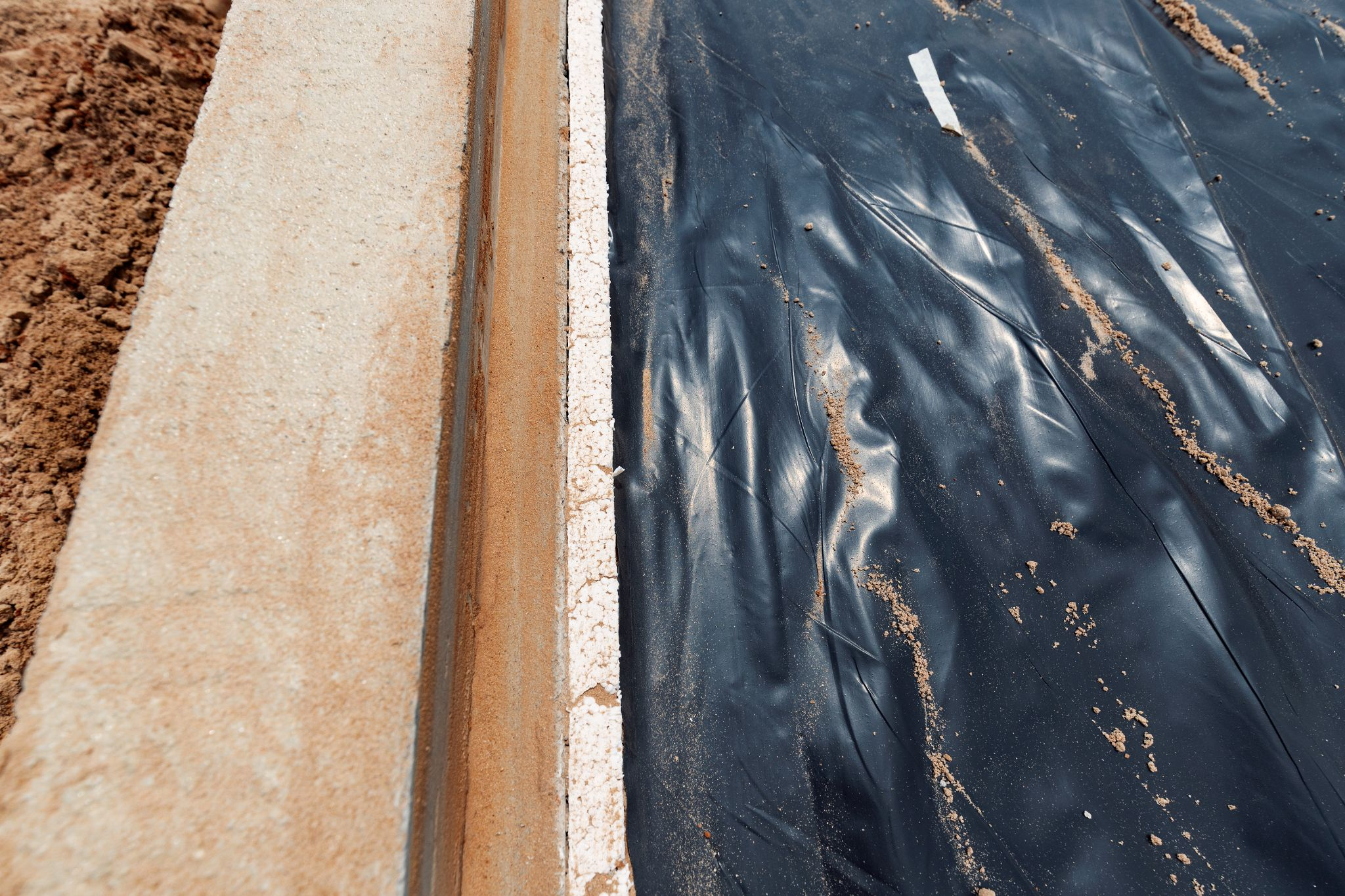 A foundation with a black tarp on it to protect the foundation