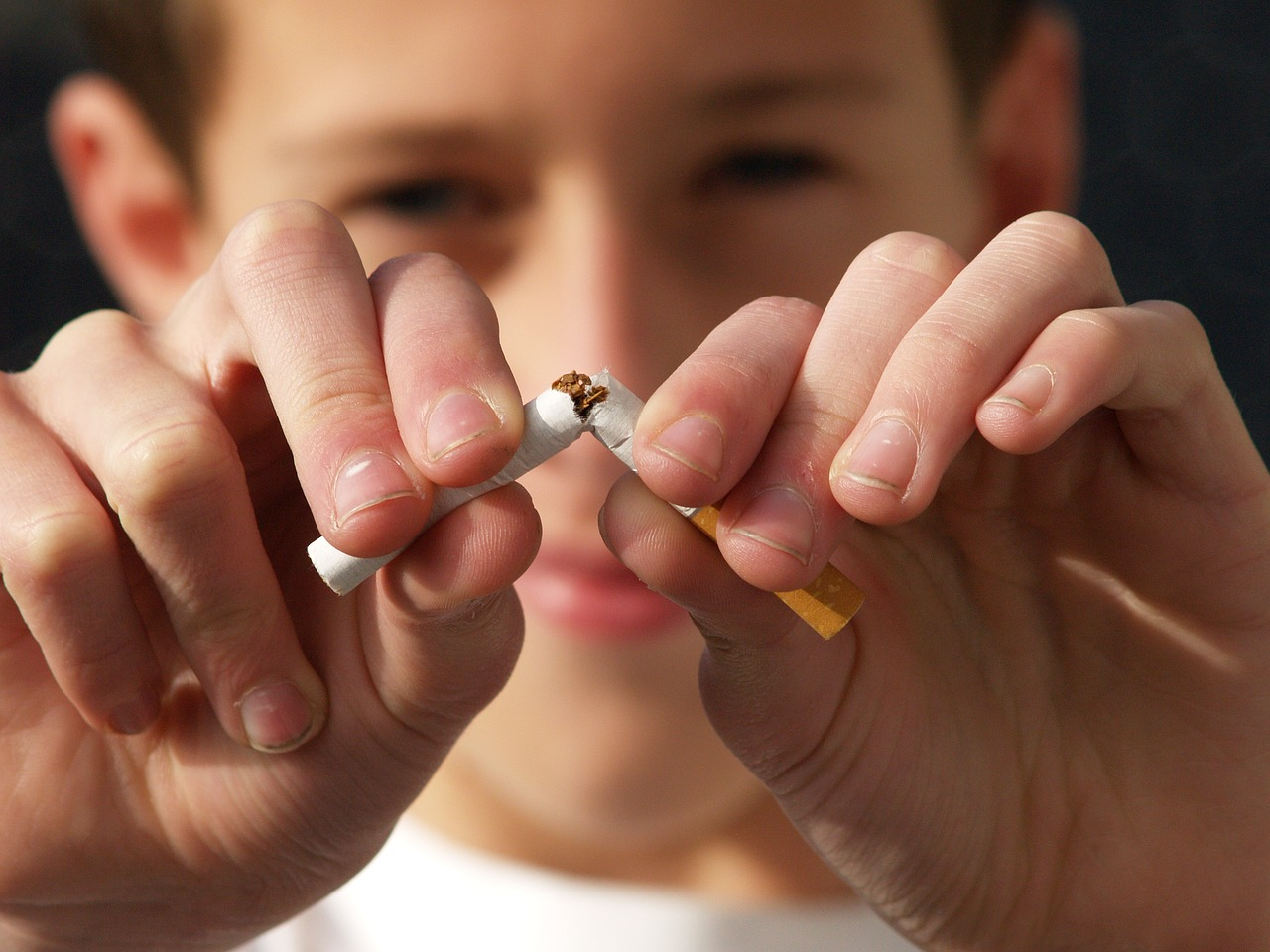 A young boy breaking a cigarette stick.