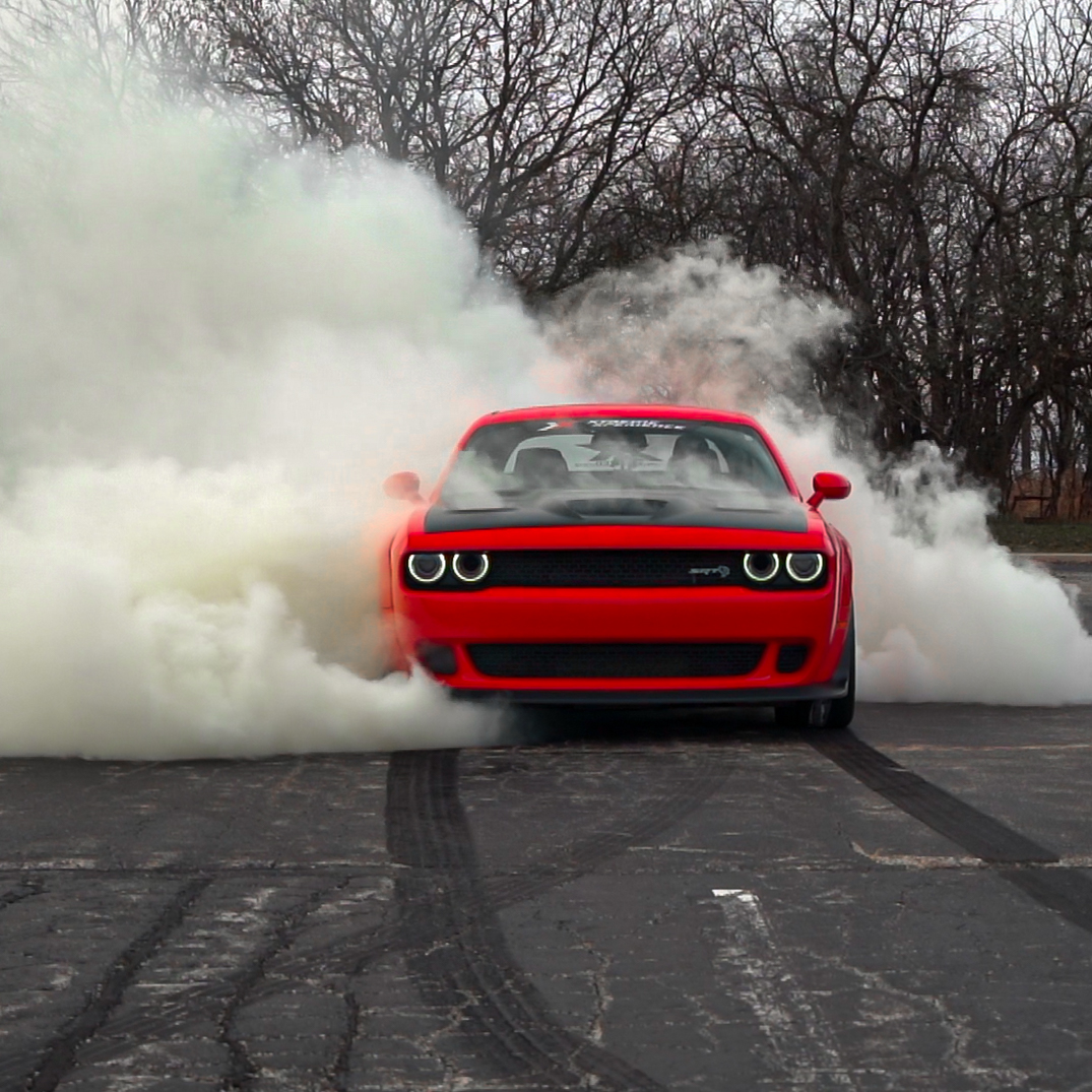 Dodge Challenger Hellcat Widebody doing a burnout with smoke pouring out of the back wheels with hot pieces of rubber coming off of the wheels.