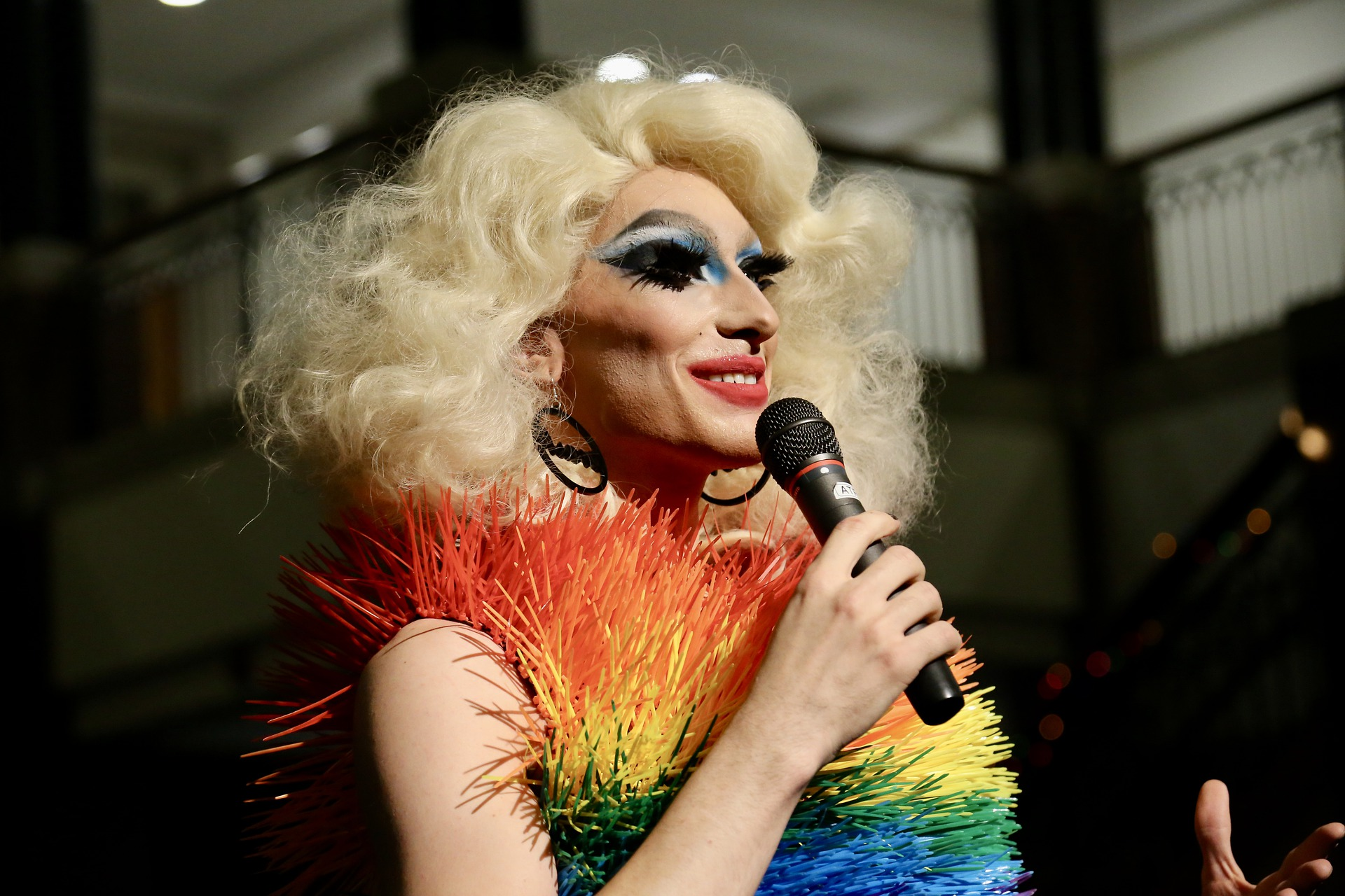 A drag queen speaking at an LGBTQ+ event.